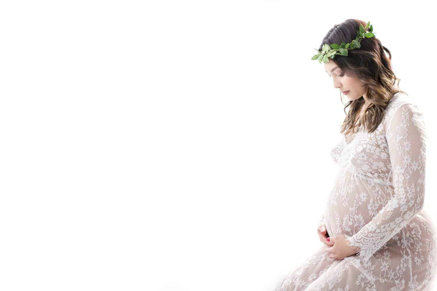 Pregnant woman in a white dress on a white background