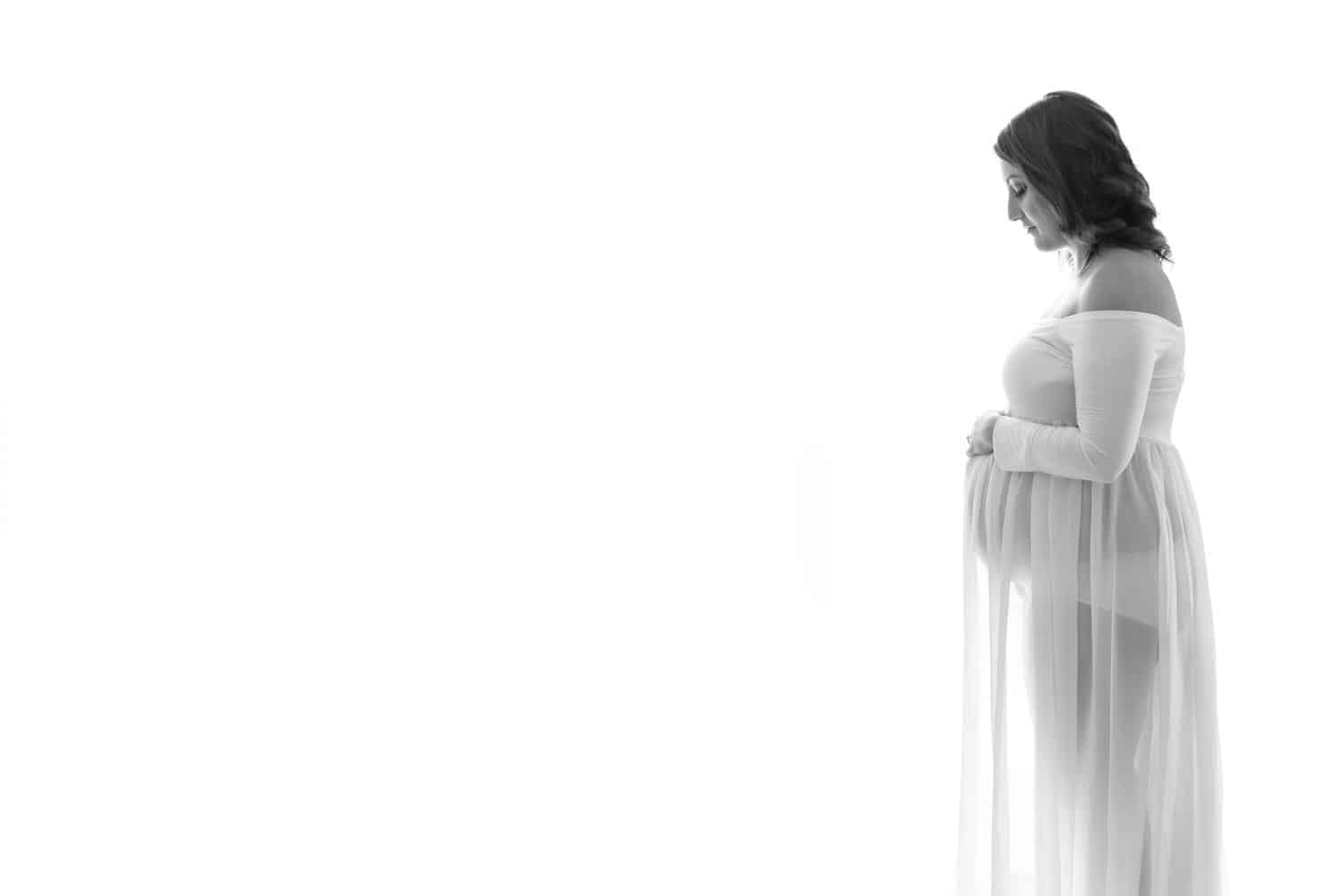 Pregnant woman wearing white dress on white background