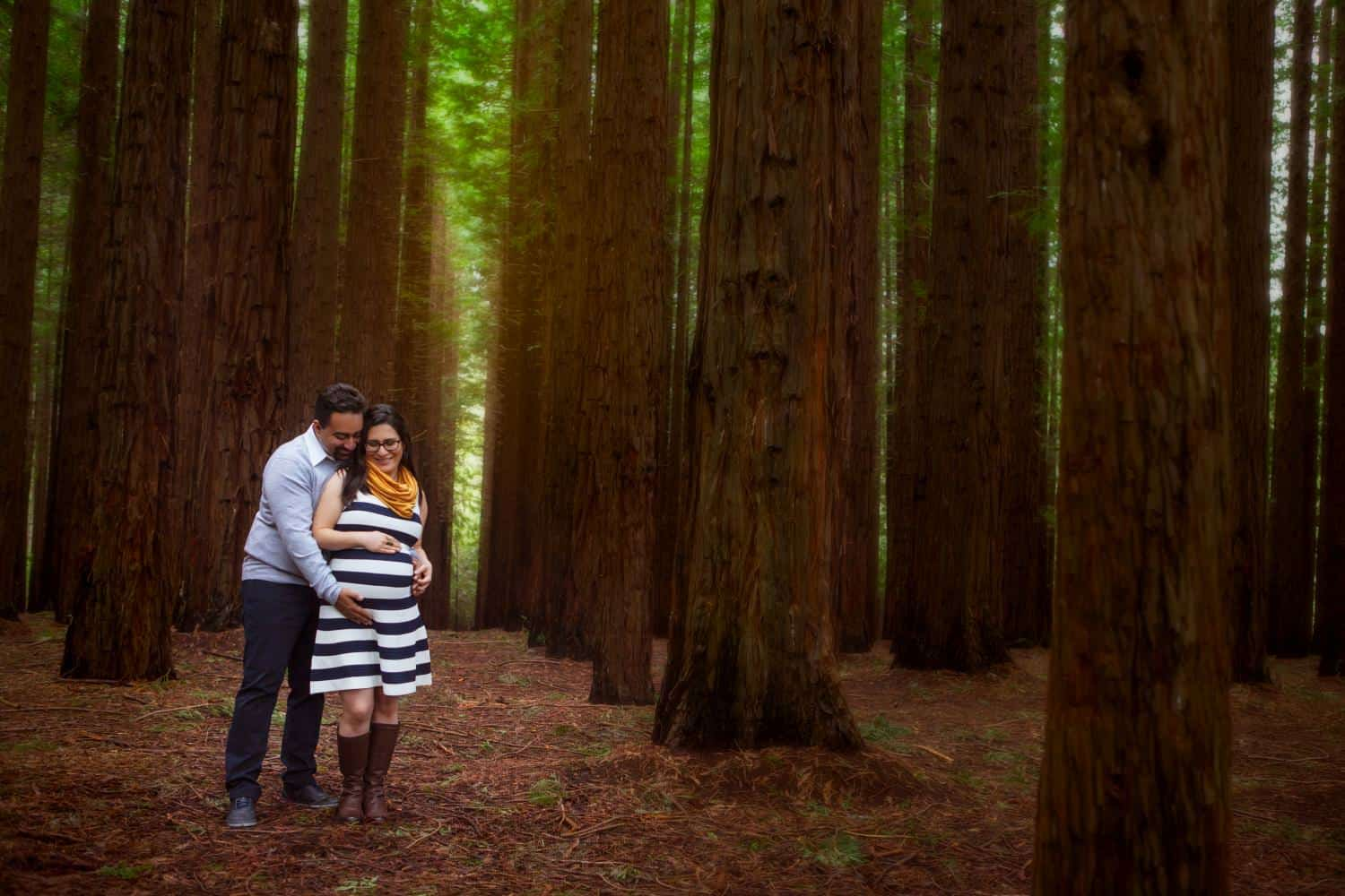 Pregnant woman and partner in a forrest