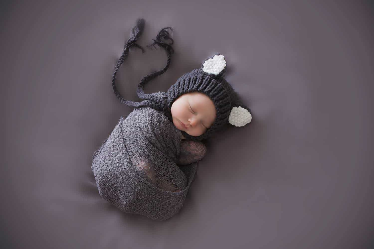 Newborn baby wrapped up on grey background