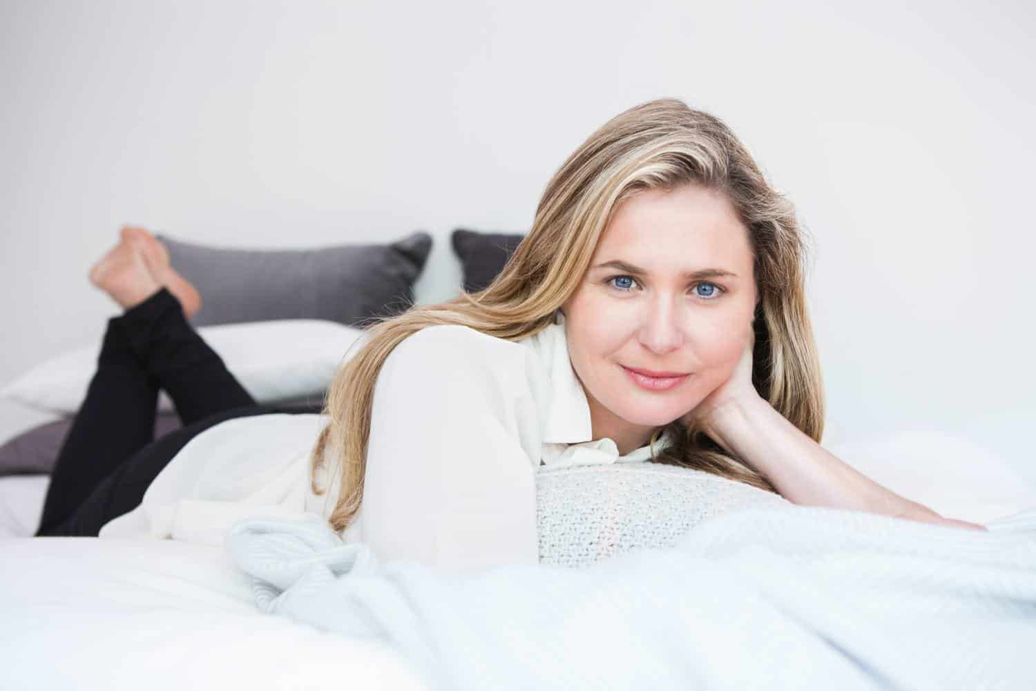 Woman laying on bed smiling at camera